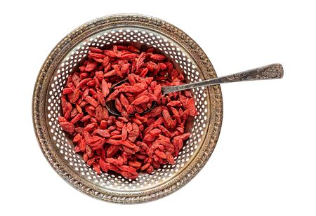 lycium: Antique metal bowl of raw dried goji berries with vintage teaspooned inside isolated on white