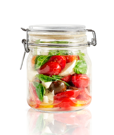 Mixed caprese salad in a closed lid glass mason jar isolated on white with reflexion
