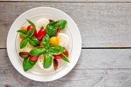 Double plated fresh farm style caprese salad on a weathered wooden board Reklamní fotografie