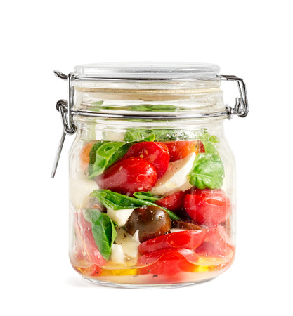 Mixed caprese salad in a closed lid glass mason jar isolated on white Reklamní fotografie