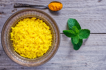 curcumin: Top view of an antique metal bowl with cooked turmeric jasmine rice, mint leaves and vintage teaspoon filled with powdered curcumin Stock Photo