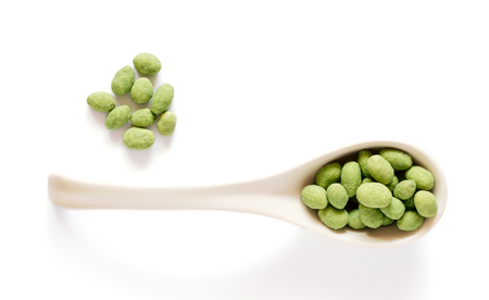 White porcelain spoon with wasabi coated peanuts isolated on white Reklamní fotografie