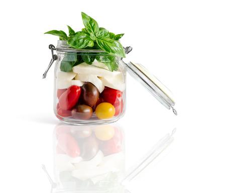 reflexion: ensalada caprese estilo fresco granja en una tapa del tarro abierto aislado en blanco con la reflexión Foto de archivo
