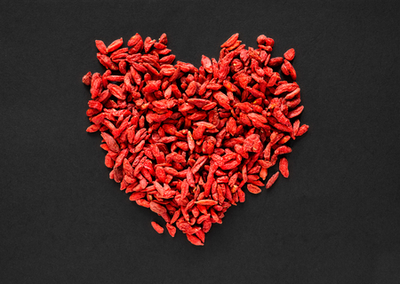 Raw dried goji berries arranged in a heart shape on a black background
