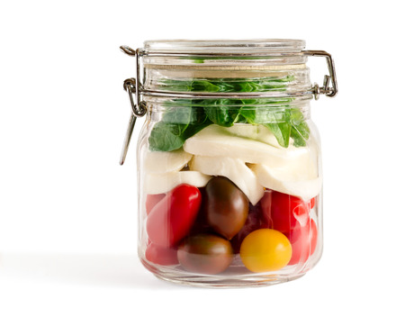 Layered caprese salad in a closed lid glass mason jar isolated on white