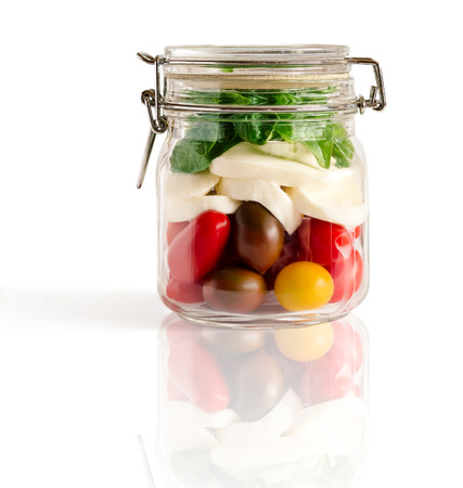 Layered caprese salad in a closed lid glass mason jar isolated on white with reflexion