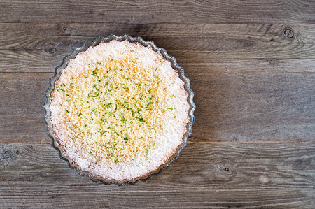 Lemon, lime, coconut impossible pie with white chocolate shavings on a weathered wooden table Reklamní fotografie