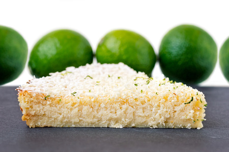 Lemon, lime, coconut impossible pie with white chocolate shavings slice on a gray slate with limes in the background