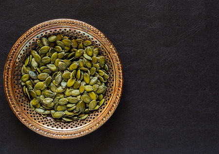 Raw pumpkin seeds in an antique meral bowl on a dark textured background Reklamní fotografie