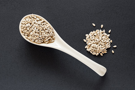 Top view of raw sunflower seeds in a porcelain spoon against a dark textured background