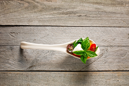 Fresh farm style caprese salad in a porcelain spoon on a weathered wooden board