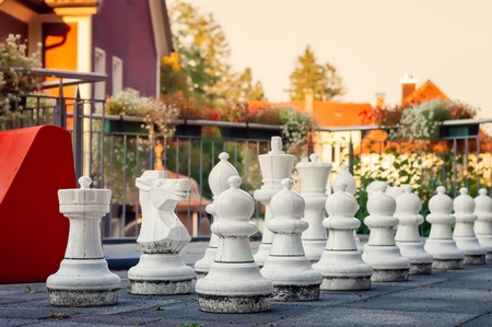 Giant white plastic outdoor chess pieces on a terrace