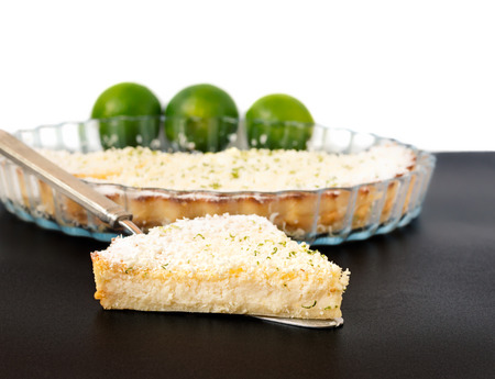 Lemon, lime, coconut impossible pie with white chocolate shavings slice on a silver cake server with limes and dish in the background