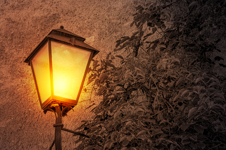 Cast iron wall mounted street lamp glowing in the dark with desaturated background Reklamní fotografie - 65666479