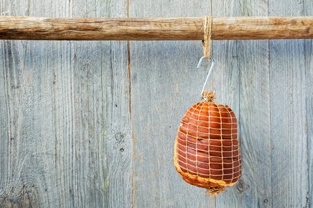 hock: Smoked boneless pork ham hock wrapped in netting hanging on a hook from a wooden pole with a weathered wood background