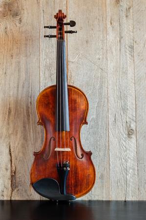 Standard violin made of wood in upright position on a black wooden table Reklamní fotografie - 68624768
