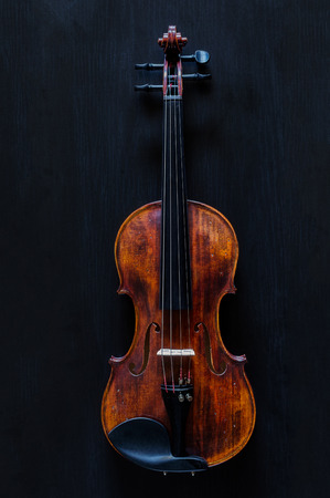 Standard vintage violin made of wood on a black wooden surface Reklamní fotografie - 65721026