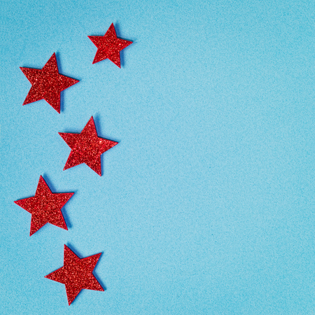 Red shining stars on the left side of a light blue textured background Reklamní fotografie
