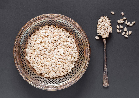 Antique metal bowl of raw dehulled sunflower seeds on a dark textured background with a vintage metal spoon on the side