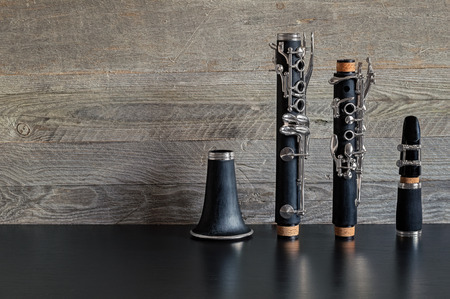 Black clarinet dismantled in four parts on a black table with a gray weathered wooden background Reklamní fotografie - 70301960