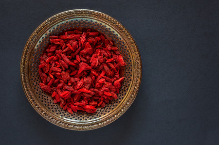 Raw dried goji berries on a vintage metal plate on a black background Reklamní fotografie