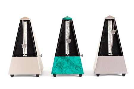 Three pyramid shaped metronomes in plastic housing isolated on white
