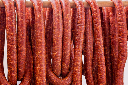 Row of smoked pork sausage in natural casings hanging on a wooden pole to dry Stock Photo