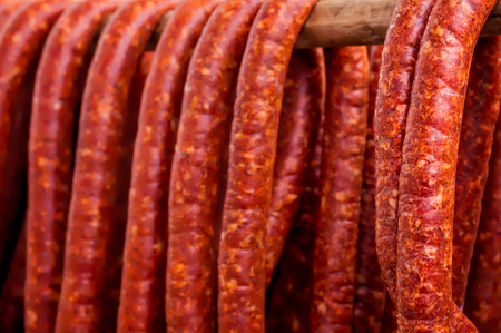 Row of smoked pork sausage in natural casings hanging on a wooden pole to dry Reklamní fotografie - 68542814