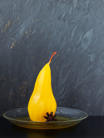 Single pear poached in sugar and saffron syrup spiced with star anise on a glass plate with a gray slate background Reklamní fotografie - 71292712