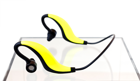 Yellow and black bluetooth earphones on an acrylic box on a white background Reklamní fotografie - 71303459