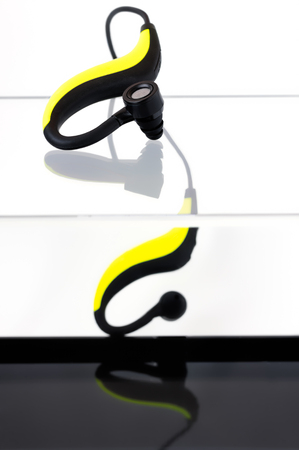 Yellow and black bluetooth earphones on an acrylic box with a black bottom