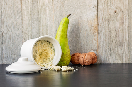 Blue cheese in white ceramic container, single pear and three walnuts on a black table with a weathered wood background Reklamní fotografie - 71303462