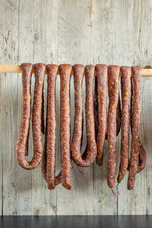 Row of smoked pork sausage in natural casings hanging on a wooden pole to dry Reklamní fotografie - 74468238