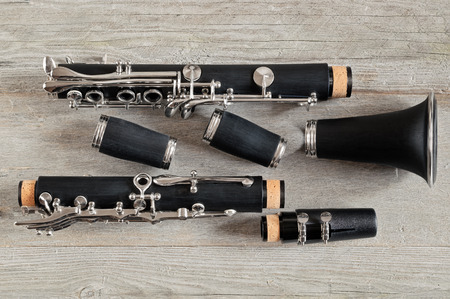 Top view of a black clarinet dismantled in four parts on a gray weathered wooden background