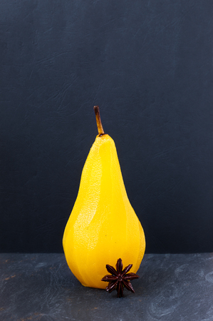 light slate gray: Single pear poached in sugar and saffron syrup spiced with star anise on a gray slate with dark textured background Stock Photo
