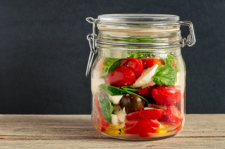 Mixed caprese salad in a closed lid glass mason jar on a wooden table with dark gray background Reklamní fotografie
