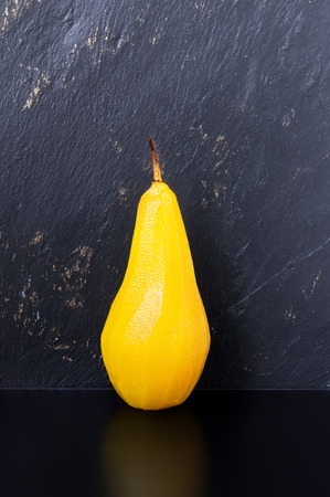 Single pear poached in sugar and saffron syrup on a black table with dark textured slate background Reklamní fotografie - 78617565