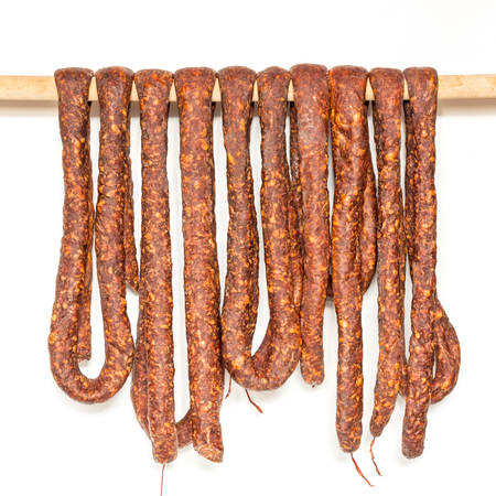 Row of smoked pork sausage in natural casings hanging on a wooden pole to dry isolated on white