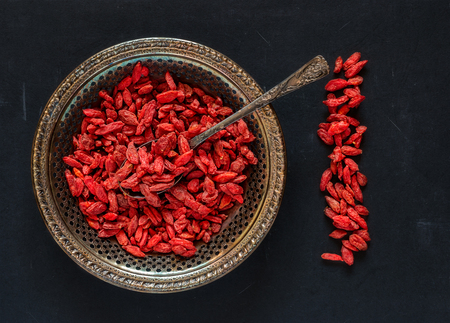 Raw dried goji berries on a vintage metal plate with spoon on a black scratched background Reklamní fotografie - 80270875
