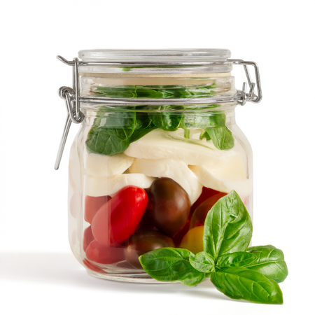 Fresh farm style layered caprese salad in an closed lid mason jar before adding dressing with basil sprig in front isolated on white. Reklamní fotografie - 80270937