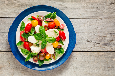 Top view of double plated fresh farm style caprese salad on a weathered wooden board