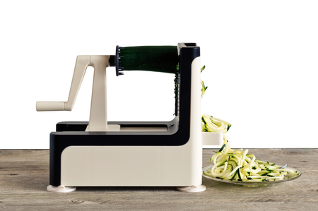 Lateral view of vegetable spiralizer making raw zucchini noodles (zoodles) .