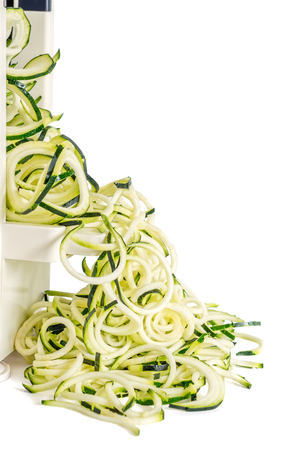 Lateral view of vegetable spiralizer  making raw zucchini noodles (zoodles) isolated on white.