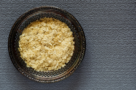Top view of dried nutritional yeast flakes on a vintage metal plate on a gray, textured background