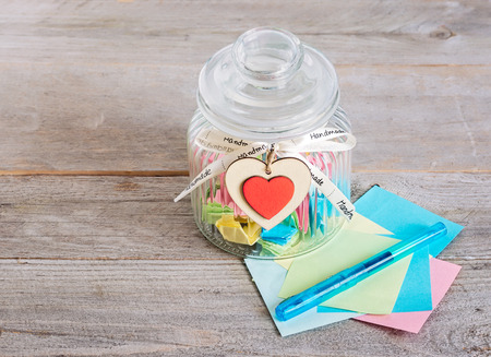 Glass jar with handmade wooden hearts decorations and ribbon near a stack of colored papers and a blue pen. Stockfoto