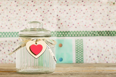 Empty glass jar with handmade wooden heart decoration and ribbon on a wooden plank with colorful pastel background.