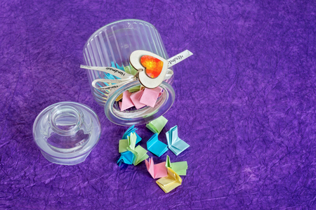 Toppled over glass jar with handmade wooden hearts decorations and ribbon full of colorful folded paper slips. Reklamní fotografie - 83493817
