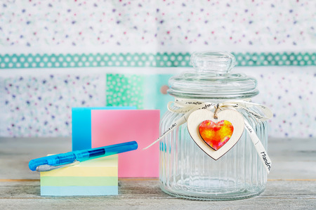 Glass jar with handmade wooden hearts decorations and ribbon near a stack of colored papers and a blue pen. Reklamní fotografie - 83954107