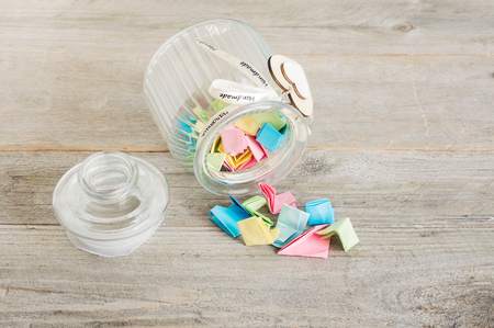Glass jar with handmade wooden hearts decorations and ribbon filled with colorful pastel paper notes spilling over. Stock Photo