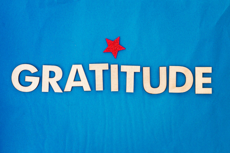 Top view of capital letters made of wood spelling the word gratitude with a red shiny star and blue background. Reklamní fotografie - 83954116